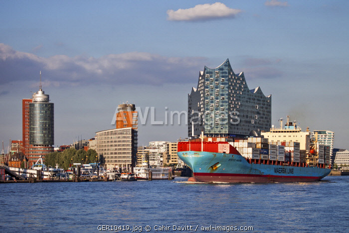 The Danish flagged container ship, the Nysted Maersk leaving Hamburg Port with the Elbphilharmonie and the Hanseatic Trade Center in the background, Hamburg Mitte, Hamburg, Germany.