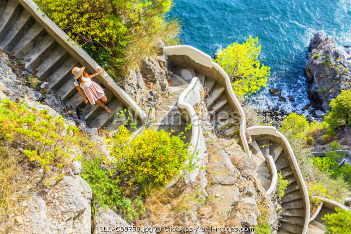 awl-images.com - Italy / Praiano, Amalfi coast, Salerno, Campania, Italy. Girl goes down along a stairway to the sea (MR)