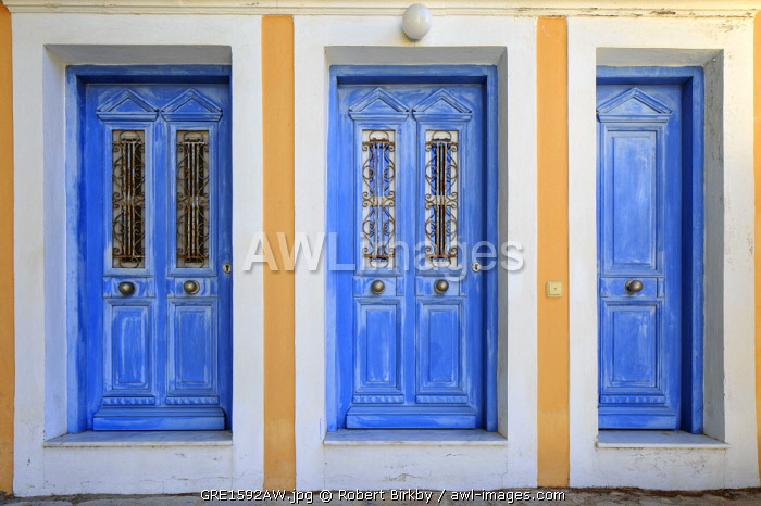 Greece, Symi, Chorio. Three ornate and brightly painted doors.