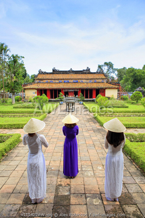 Asia, South East Asia, Vietnam; Hue, young women praying and wearing traditional Ao Dai dresses and Non La conical hats outside Gia Long tomb, MR