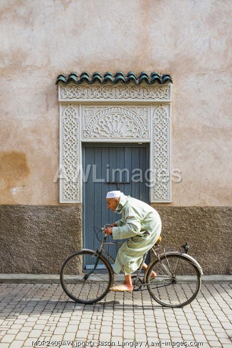 Morocco, Marrakech-Safi (Marrakesh-Tensift-El Haouz) region, Marrakesh. A man wearing a djellaba walks past a decorative doorway in the medina (old town).