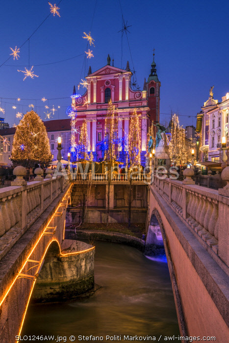 Franciscan Church of the Annunciation and Triple Bridge or Tromostovje adorned with Christmas lights, Ljubljana, Slovenia