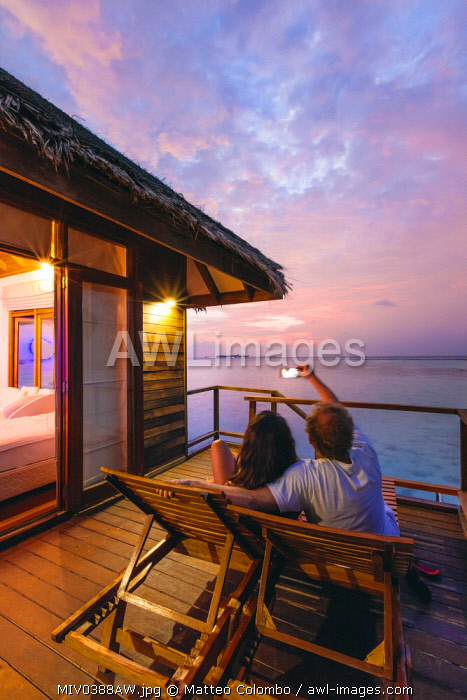 Couple watching sunset from overwater bungalow, Maldives (MR)