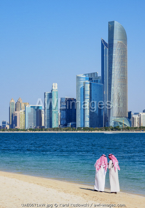 Two men wearing thawb on the beach and City Center Skyline, Abu Dhabi, United Arab Emirates