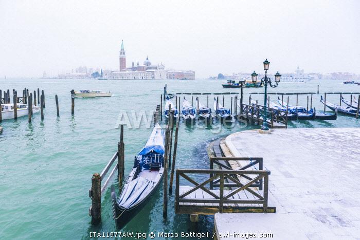 Gondolas with snow at St Mark's waterfront, Venice, Veneto, Italy.