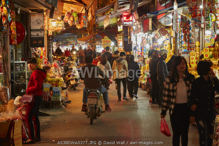 Motorcycle and shoppers in night market, Old Quarter, Hanoi, Vietnam