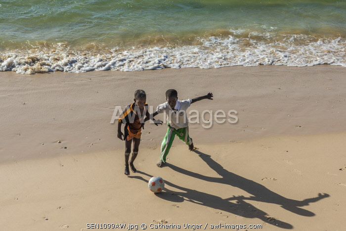 Africa, Senegal, Saint-Louis. Children playing football on the beach of Saint-Louis.