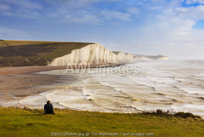 A man watches the stormy sea at Seven sisters, East Sussex, England