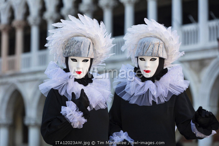 Two poseurs dressed as identical twins pose in St Mark's Square during the Venice Carnival, Venice, Italy