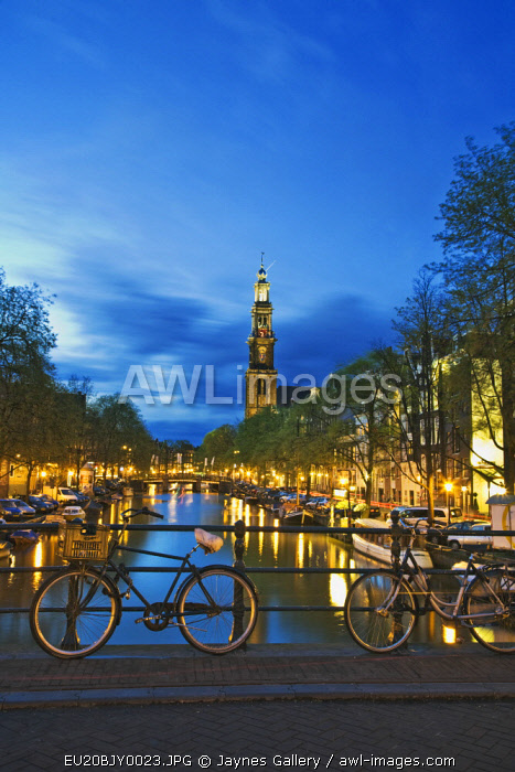 Netherlands, Amsterdam. Bikes on bridge over canal at sunset.