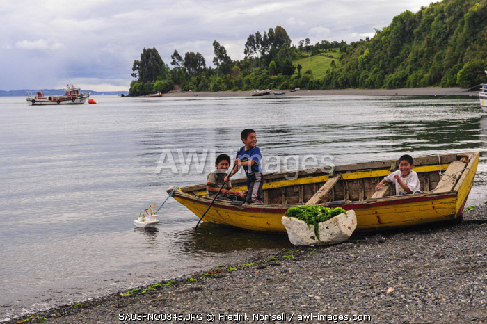 Chile, Patagonia, Lake District. Children playing with their model fishing boat made from styrofoam.