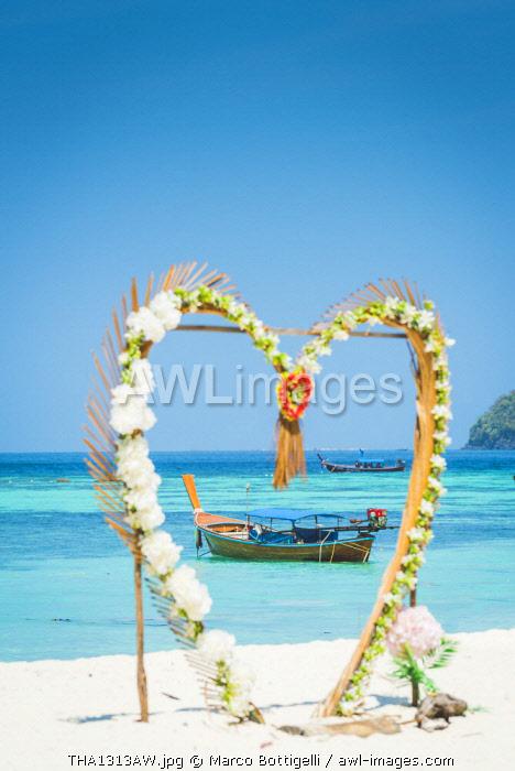Ko Lipe, Satun Province, Thailand. Traditional long tail boats through a heart shape decoration on the beach.