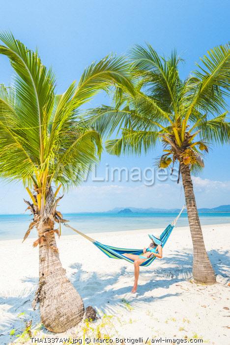 Ko Muk (Ko Mook), Trang Province, Thailand. Beautiful woman relaxing on hammock on the beach (MR).