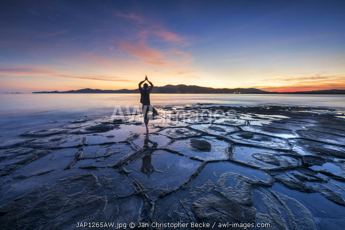 Man doing yoga exercise at the Tatami-ishi rocks on Kumejima island, Okinawa, Japan (MR)