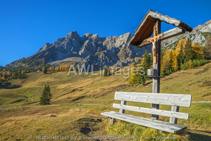 Wooden cross and bench, behind it the Eisenspitze, Dawin-Alpe, Strengen am Arlberg, Tyrol, Austria, Europe