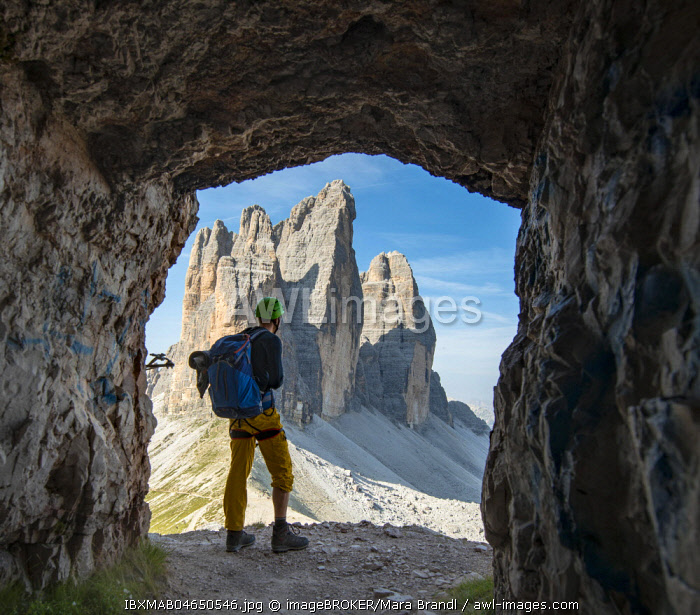 Hiker at the via ferrata to the Paternkofel, view from war tunnel, north faces of the Three Peaks of Lavaredo, Sexten Dolomites, South Tyrol, Italy, Europe
