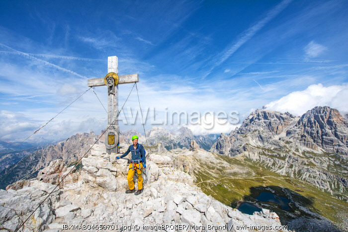 Hiker at the peak cross of the Paternkofel, Sexten Dolomites, South Tyrol, Trentino-South Tyrol, Alto-Adige, Italy, Europe