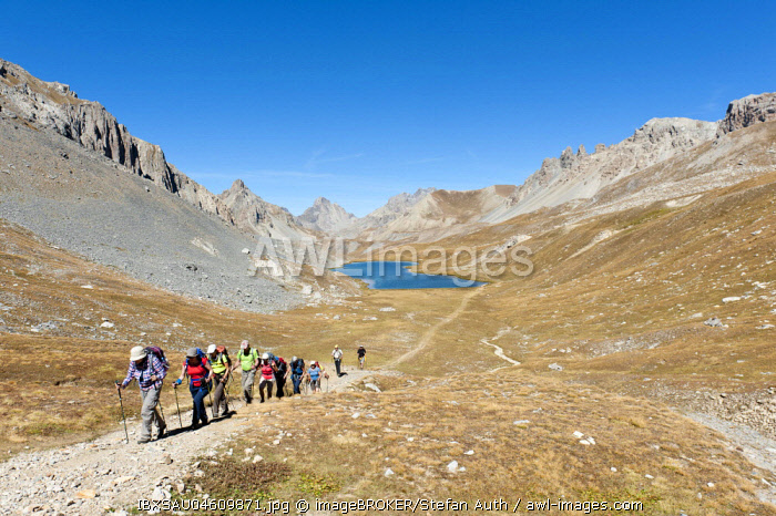 Hiking group at the Lac de l' Oronaye mountain lake, mountain landscape near Larche, Commune nouvelle Val d' Oronaye, Departement Alpes-de-Haute-Provence, France, Europe