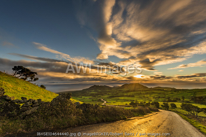 Road through green hilly countryside at sunrise with clouds, island of Pico, Azores, Portugal, Europe