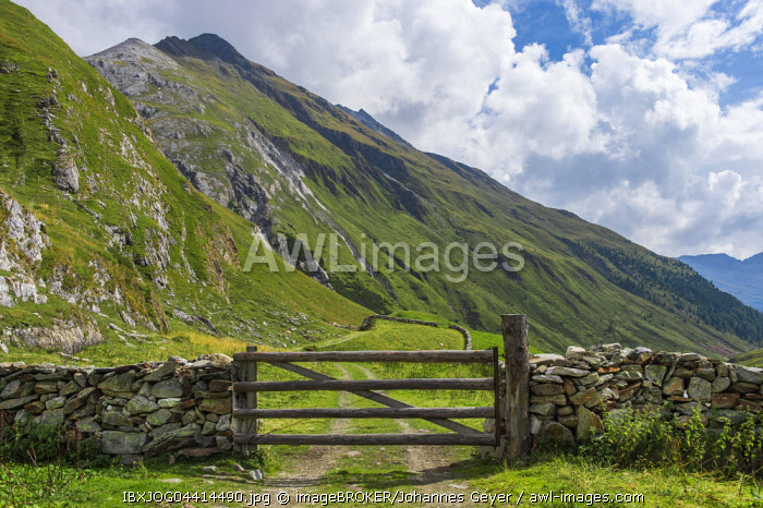 Natural stone wall with wooden gates , mountain landscape, Defereggen Valley, High Tauern National Park, Central Eastern Alps, East Tyrol, Austria, Europe