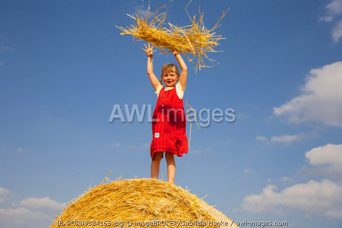 Little girl standing on a bale of straw throwing straw, Germany, Europe