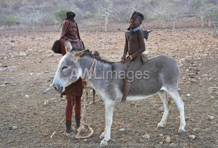 Married Himbafrau with girl on a donkey, Kaokoveld, Namibia, Africa