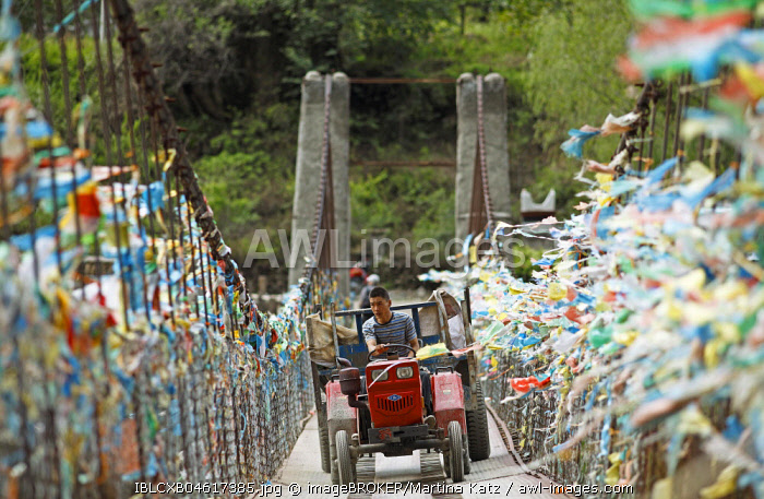 Farmer drives with a tractor over a suspension bridge decorated with prayer flags, Jiaju Village, autonomous district Garzê of the Tibetans, Sichuan, China, Asia