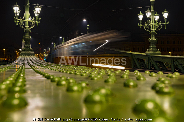 Parapet of the Liberty Bridge with driving tram at night, Budapest, Hungary, Europe