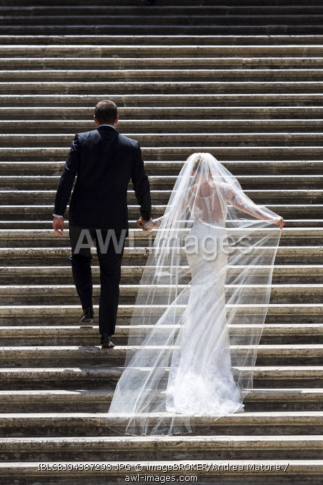 Bride and groom walking up a staircase