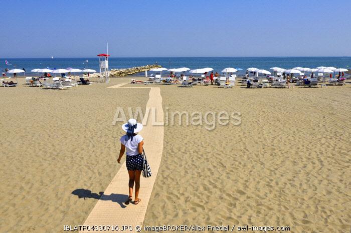 Woman walking on the beach, Lido di Venezia city beach, Venice, Veneto, Italy, Europe