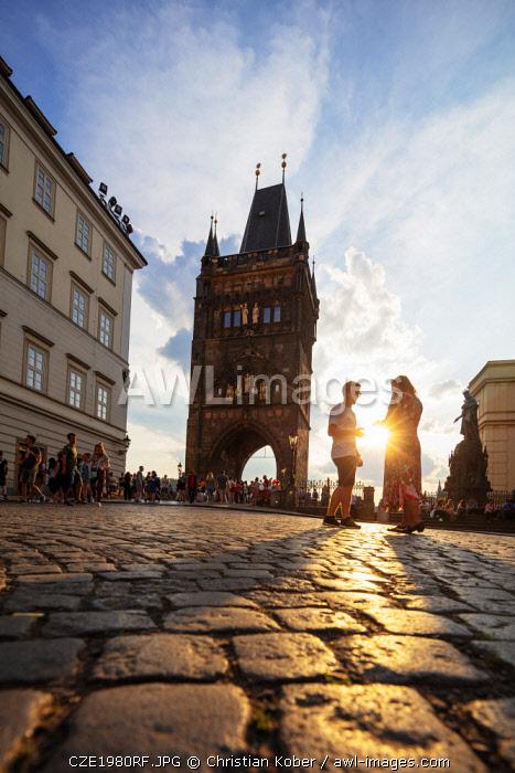Europe, Czech Republic, Bohemia, Prague, Unesco site, Charles bridge, tourist on cobble stone street at sunset