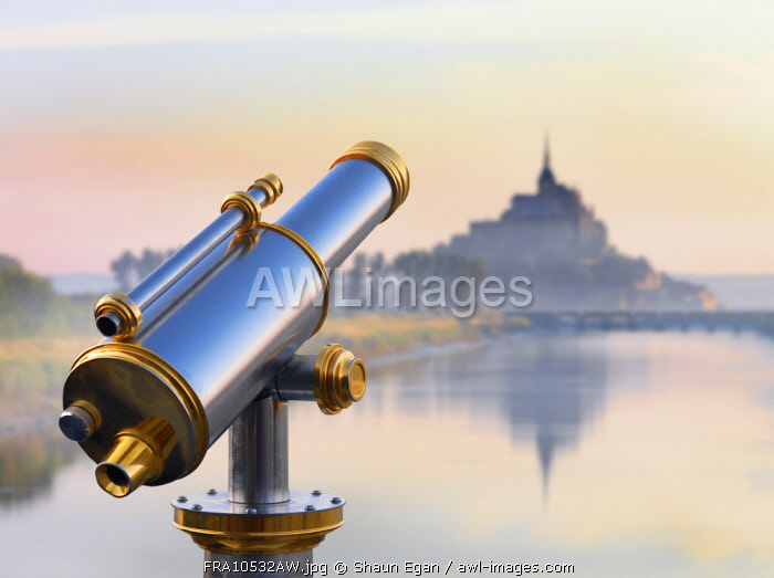 France, Normandy, Le Mont Saint Michel, shrouded in fog at dawn, reflected in river, telescope in foreground