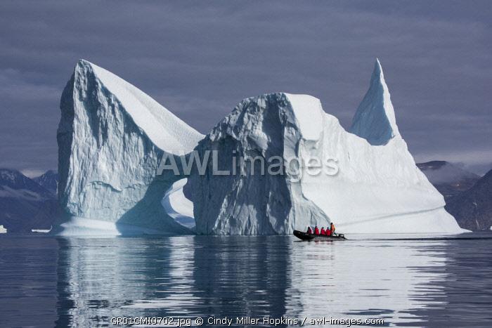 Eastern Greenland, Scoresbysund, aka Scoresby Sund, Bear Island, aka Bjorne Oer. Adventure tourists exploring huge icebergs from zodiac. (For Editorial Use Only)