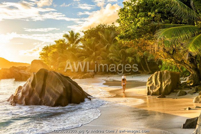 A young woman enjoys the sunrise on Anse Patates beach. La Digue, Seychelles, Africa (MR)