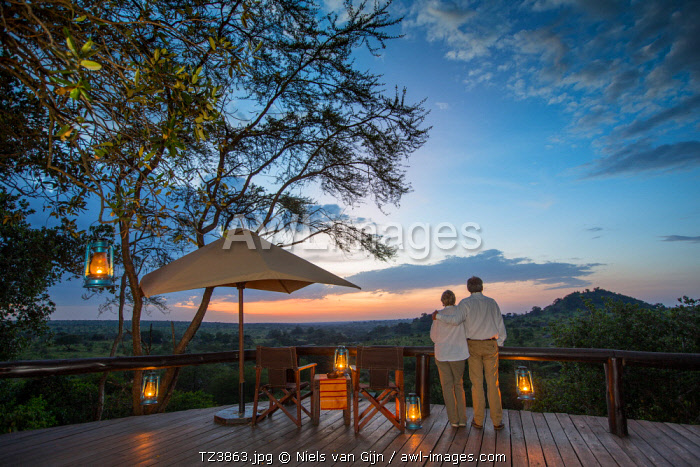 Tanzania, Serengeti, Migration Camp, Elewana, a couple relax with sundowners on the deck at sunset.