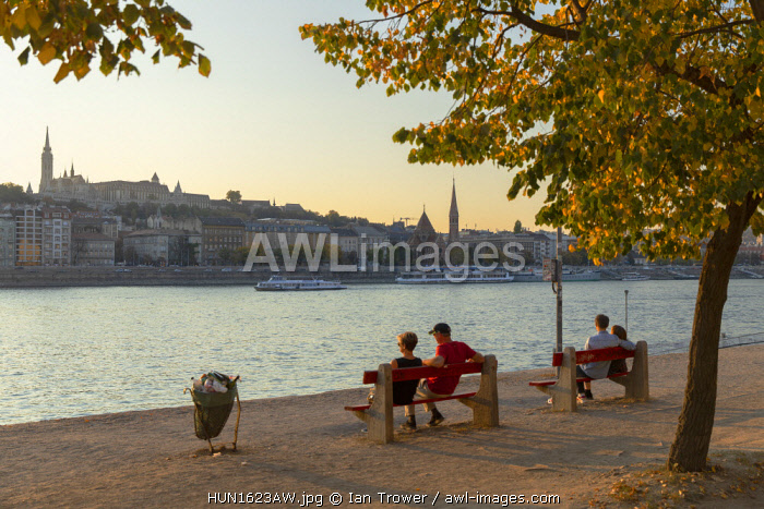 People sitting alongside River Danube, Budapest, Hungary