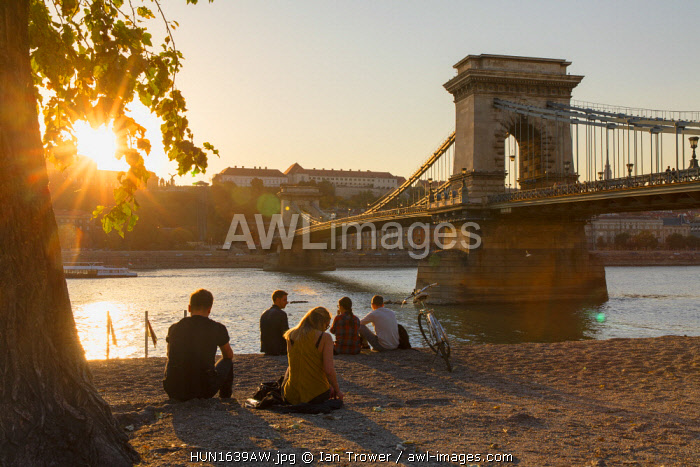 People sitting next to Danube River and Chain Bridge (Szechenyi Bridge), Budapest, Hungary
