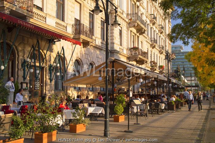 People walking past outdoor restaurants along Danube Promenade, Budapest, Hungary