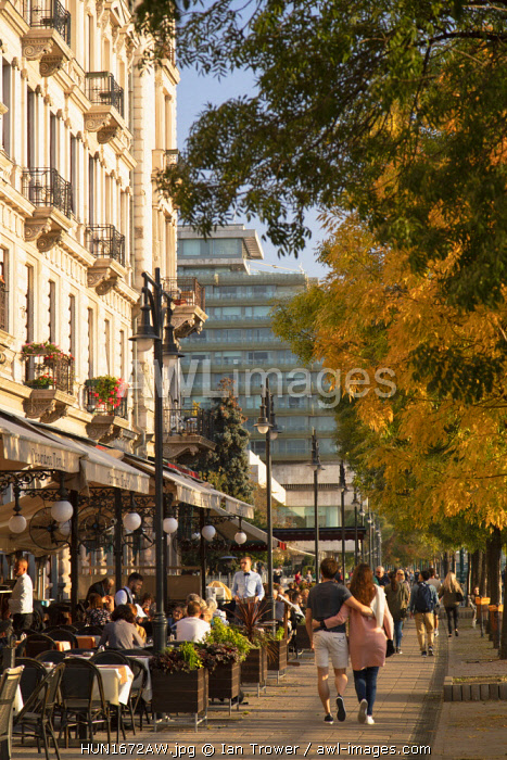 People walking past outdoor restaurants along Danube Promenade, Budapest, Hungary