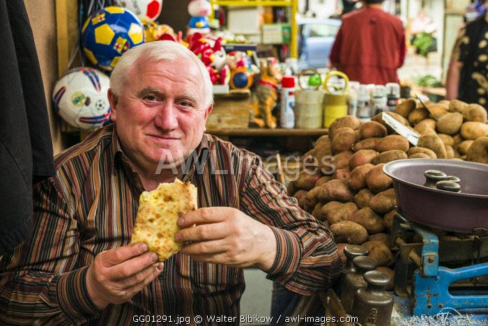 Georgia, Kutaisi, Kutaisi Market, vendor eating lunch