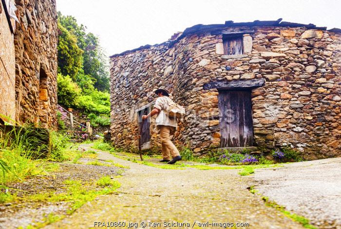 France, Occitane, Saint Gervais sur Mare. Pilgrim of Santiago de Compostela walking passing through the old hamlet of Mecle towards Santiago de Compostela on the Via Tolosana. MR