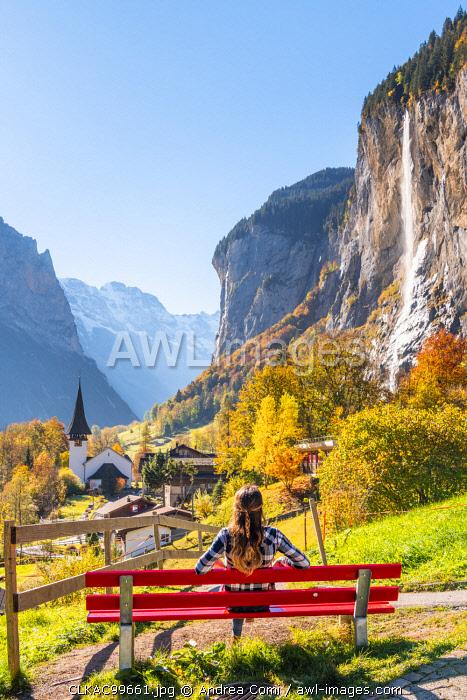 A young woman admires Lauterbrunnen village. Lauterbrunnen, Canton of Bern, Switzerland, Europe (MR)