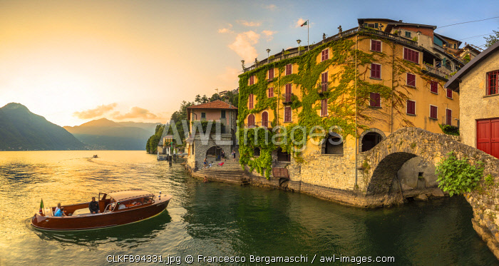 A boat of tourists stops to observe the sunset. Nesso, Province of Como,  Como Lake, Lombardy, Italy, Europe.