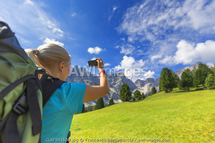 Girl take a photo with a smartphone. Longiarù, Badia Valley, South Tyrol, Dolomites, Italy, Europe. (MR)