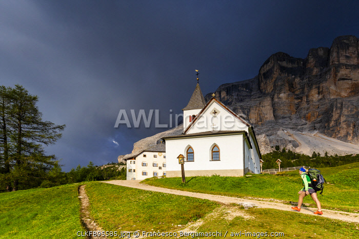 Hiker walk on a path near Santa Croce Sanctuary with coming thunderstorm. La Valle/La Val/Wengen Badia Valley, South Tyrol, Dolomites, Italy, Europe. (MR)