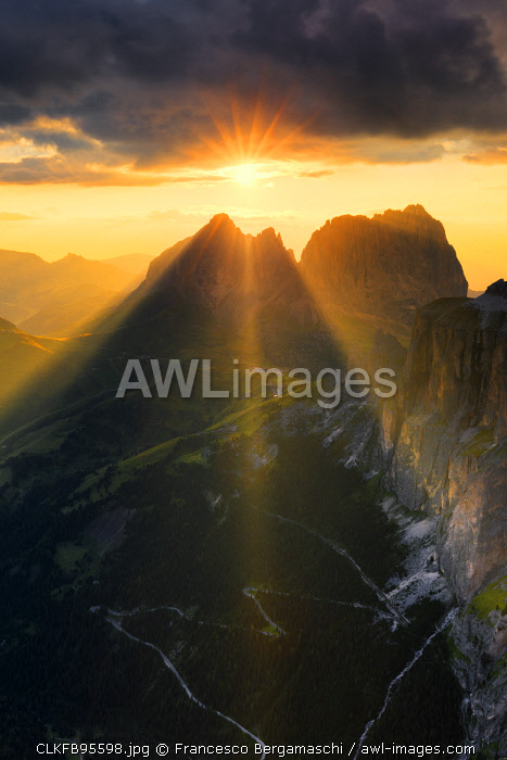 Sun rays filters between stormy clouds during sunset with Sassolungo group in the foreground. Fassa Valley, Trentino, Dolomites, Italy, Europe.