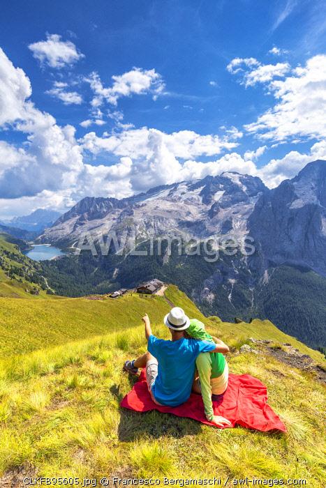 Tourists looks Viel del Pan Refuge with Marmolada in the background. Pordoi Pass, Fassa Valley, Trentino, Dolomites, Italy, Europe. (MR)