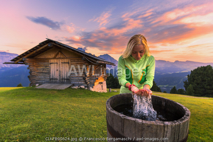 Girl washes herself in a tube at sunset. Gardena Valley, South Tyrol, Dolomites, Italy, Europe. (MR)