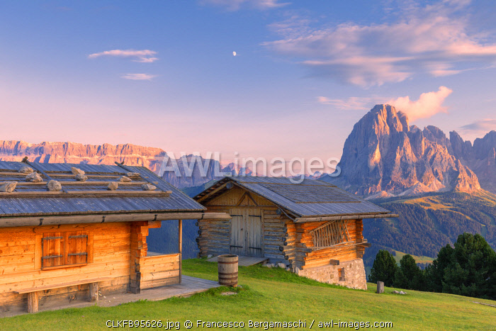 Traditional huts at sunset with Sassolungo and Sella Group in the background. Gardena Valley, South Tyrol, Dolomites, Italy, Europe.
