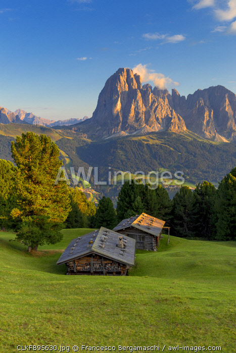 Last rays of sun on traditional hut with view on Sassolungo Group. Gardena Valley, South Tyrol, Dolomites, Italy, Europe.